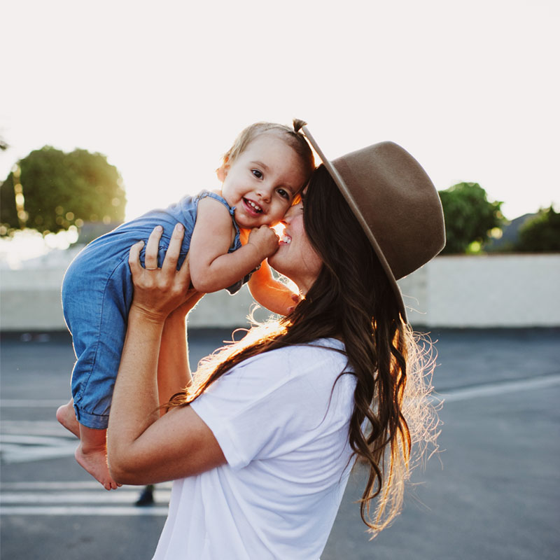 Woman wearing hat holding smiling baby